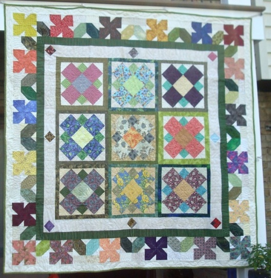 I learned a lot from In Full Bloom. Each block is a separate quilting motif, so I machine quilted it block by block... and subsequently had to tie off ALL those ends.
